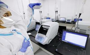 唾液を用いたPCR検査施設で行われる作業=24日午後、千葉県市川市の国立国際医療研究センター国府台病院