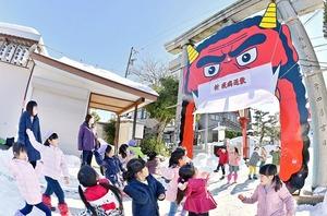 マスクをした巨大な鬼の面に元気よく雪玉を投げる園児=1月20日、福井県福井市の和田八幡宮