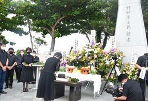 沖縄県豊見城市の旧日本海軍司令部壕で営まれた慰霊祭で手を合わせる参列者=13日午前
