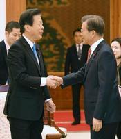 公明党の山口代表(左)と握手する韓国の文在寅大統領=23日、ソウル(共同)