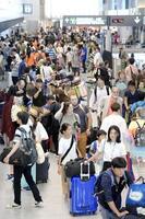 混雑する成田空港の到着ロビー=18日
