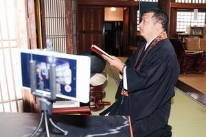 スマートフォンで動画を撮り配信している泰圓澄一法さん=8日、福井県越前市の長慶寺