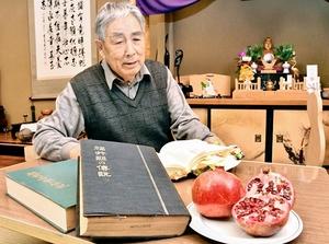 ザクロを食べない風習を説明する男性。書物には由来となった菅原道真の伝説が記されている=福井県福井市天菅生町