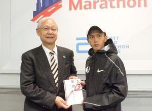 シカゴ・マラソンで日本新記録を出し、日本実業団陸上連合から1億円の目録を受け取る大迫傑=シカゴ(共同)
