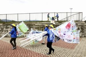 台風に備え、国体サッカー会場の応援のぼり旗や応援幕を片付ける関係者=9月30日、福井県坂井市丸岡スポーツランド