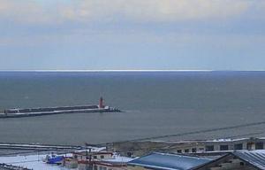 北海道網走市内から確認された流氷(中央奥)=13日午後(網走地方気象台提供)