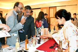 8日、ニューデリーの日本大使公邸で開かれた試飲会で、日本酒に関する説明を受けるインド人ら(共同)