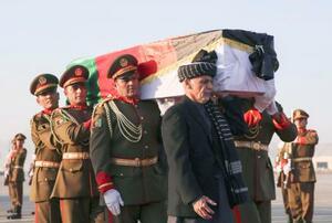 7日、カブールの空港でアフガニスタンのガニ大統領(手前右端)と軍兵士らに運ばれる中村哲さんのひつぎ(AP=共同)