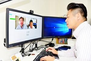 都内で在宅勤務する日景学さん(画面左)とテレビ会議をする斎藤智示さん=福井市中央1丁目の「ビットブレイン」