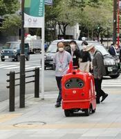 実験のため公道を走る日本郵便の自動配送ロボット=2020年10月、東京都千代田区