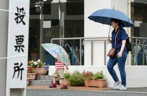 福岡県久留米市の投票所に向かう有権者ら。大雨の影響で投票開始時刻が2時間遅れた=21日午後