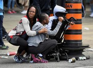 米NBAラプターズの優勝パレードで発砲があり、避難する人々=17日、カナダ・トロント(ロイター=共同)