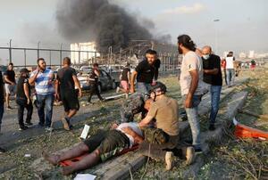 爆発の負傷者を救助する人たち=4日、ベイルート(AP=共同)