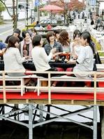 堂田川の川床にしつらえた「川床レストラン」で地元ならではの料理を楽しむ参加者=10日、福井県福井市東郷二ケ町