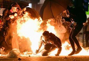 香港理工大周辺で他のデモ参加者が投げた火炎瓶の火に巻き込まれるデモ隊=18日夜、香港(共同)
