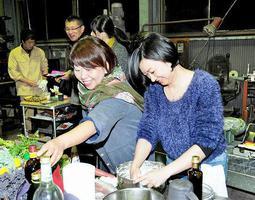 香港から福井県を訪れ 県産食材を使った料理を作る趙燕メイさん(右)=3日夜、福井市北楢原町のTAYASU