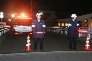 女性の遺体が見つかった現場付近を規制する愛媛県警の警察官=13日午後8時18分、愛媛県今治市