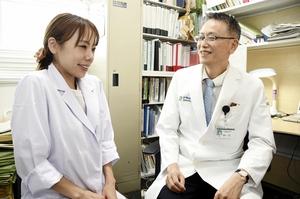 両肩をすぼめるストレッチなどで筋肉をほぐすよう呼び掛ける浜野忠則教授(右)=福井大学医学部附属病院