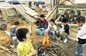 外遊びの合間にたき火を囲む子どもたち=福井県坂井市春江町井向