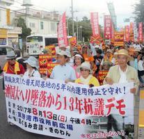 米軍ヘリ墜落事故から13年を迎え、沖縄国際大での集会後、米軍基地の危険性を訴えデモ行進する人たち=13日午後、沖縄県宜野湾市