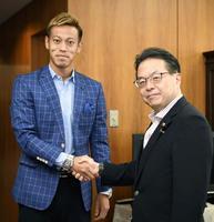 会談前に握手する世耕経産相(右)とサッカー日本代表の本田圭佑選手=21日午前、経産省
