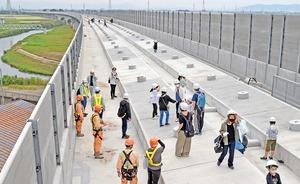 北陸新幹線の竹田川橋りょうの工事現場を見学する親子ら。左がS字に蛇行する竹田川=10月3日、福井県あわら市