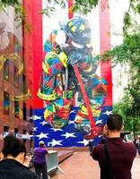 11日、米ニューヨーク中心部のビルに描かれた追悼壁画を見る市民(共同)