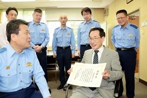 感謝状を受け取った後、高中真太郎署長(手前左)らと歓談する近藤高行さん(同右)=13日、福井県警坂井署