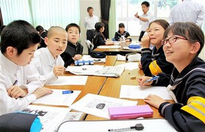 記事のテーマを話し合う生徒=18日、福井市越廼中