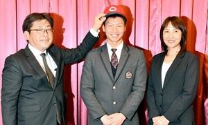 会見後、広島の高山健一スカウト(左)に帽子をかぶせてもらう木下元秀外野手(中央)。右は母・美予さん=11月14日、福井県敦賀市