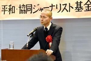 「第25回平和・協同ジャーナリスト基金賞」の贈呈式であいさつする京都新聞社取材班の森敏之記者=7日午後、東京都内