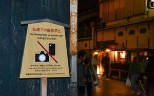 京都市東山区の「花見小路」周辺に掲げられた、私道での写真撮影を禁止するとした高札=25日夜