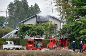 火災で煙を上げる住宅=15日午前6時44分、栃木県市貝町