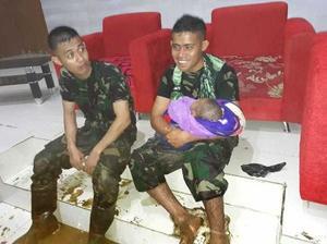 17日、鉄砲水や土砂崩れが発生したインドネシア東部パプア州ジャヤプラ近郊センタニで、救出された赤ん坊を抱く兵士(右)(インドネシア軍提供・共同)