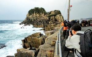 鉾島にカメラを向けるツアー参加者=2016年12月9日、福井市南菅生町
