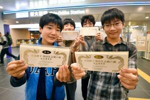 「即位礼正殿の儀」に合わせて発売された大阪メトロの記念乗車券を手に笑顔の中学生=22日午前7時24分、大阪市