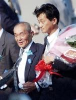 2002年10月に24年ぶりに北朝鮮から帰国した地村保志さん(右)と手を握り合う保さん=羽田空港