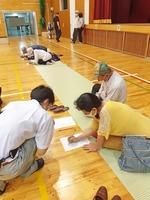 体育館内で問診票に記入する避難者。新型コロナウイルス感染防止のため、入る前に検温、問診する方針だった=6月14日、福井県の福井市安居小学校