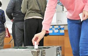 投票箱に一票を投じる県内の有権者=22日、福井市中藤島公民館