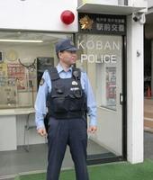 ベスト型の耐刃防護服を身に着けて交番の前に立つ警察官=9月20日、福井県福井市大手2丁目の駅前交番