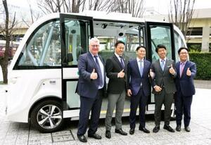 自動走行バスの前で記念撮影する茨城県境町の橋本正裕町長(中央)ら=27日午前、東京都港区