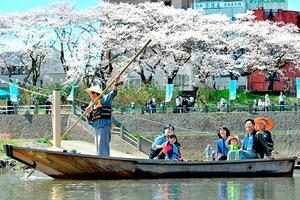 「毛矢の繰舟」で水上からの景色を堪能する人たち=2016年4月2日、福井市の九十九橋付近