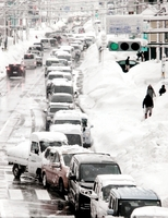 道路脇の雪で通常4車線が2車線になり渋滞した県道(通称・芦原街道)=13日午前8時5分ごろ、福井市新田塚1丁目から