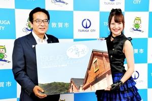 渕上隆信市長(左)からつるがふるさとサポーター認定証を受け取るぶらっくすわんさん=31日、福井県敦賀市役所