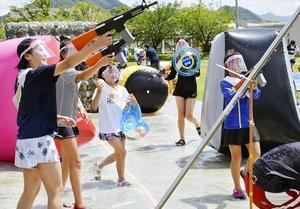 水鉄砲や水風船で大人の陣地に攻め込む子どもたち=8月14日、福井県越前市武生中央公園