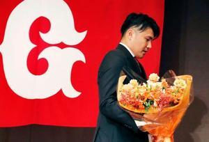 引退表明の記者会見を終え、花束を手に引き揚げる巨人の杉内俊哉投手=12日、東京都内のホテル