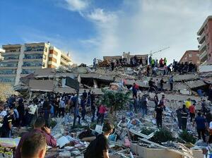 30日、トルコ・イズミル県の倒壊した建物で生存者を捜索する人々(ロイター=共同)