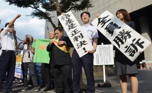 正社員との格差を一部違法と認めた判決後、「全員勝訴」の垂れ幕を掲げる弁護士と原告ら=14日午後、東京地裁前