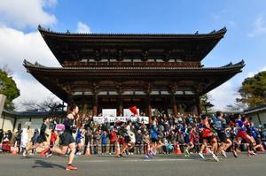 「京都マラソン2019」で世界遺産・仁和寺の前を駆け抜けるランナーたち=17日、京都市