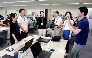Tシャツやポロシャツ、チノパン姿で打ち合わせする福井銀行の行員=福井県福井市の福銀センタービル